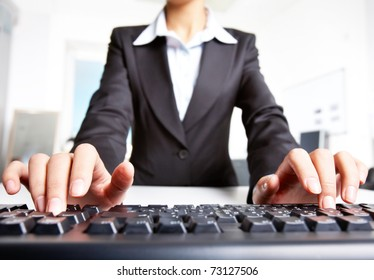 Close-up of businesswoman in black suit typing a letter