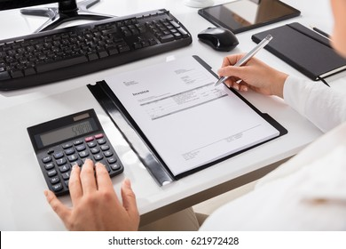 Close-up Of A Businesswoman Calculating Invoice Using Calculator On Desktop