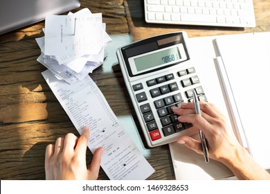Close-up Of A Businesswoman Checking Bill Over Wooden Desk In Office