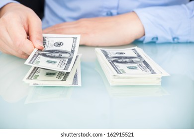 Close-up Of A Businesswoman Counting Bank Note At Desk