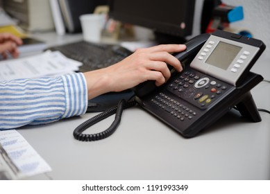 Closeup of businesswoman dialing making office phonecall, light table background. Corporate female holding telephone handle digital electronic pc connection checking daily data news, online talk job