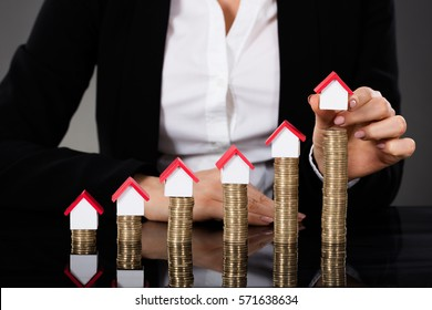Close-up Of Businesswoman Hand Arranging House Model On Stacked Coins At Desk. Property Growth Concept