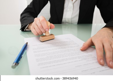 Close-up Of Businesswoman Hand Using Stamper On Document