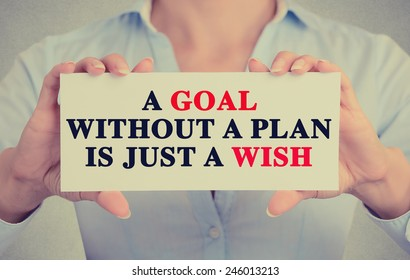 Closeup businesswoman hands holding white card sign with a goal without a plan is just a wish text message isolated on grey wall office background. Retro instagram style image