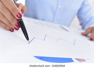 closeup of a businesswoman at her office desk full of graphs and charts, observes a chart with an upward trend