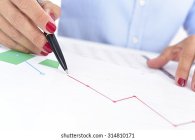 closeup of a businesswoman at her office desk full of graphs and charts, observes a chart with a downward trend