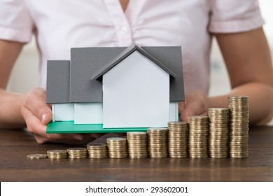 Close-up Of Businesswoman Holding House Model With Stack Of Coins At Desk