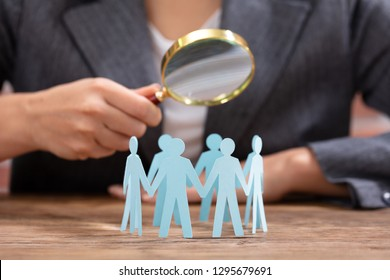 Close-up Of Businesswoman Holding Magnifying Glass Over The Human Figures Forming Circle