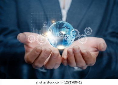 A closeup of businesswoman holding a mechanism consisting of cogwheels with currency unit icons inside, global map and growth diagram in her hands. The concept of successful global financial system.