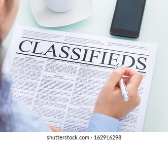 Close-up Of A Businesswoman Holding Pen Reading Classifieds On Newspaper
