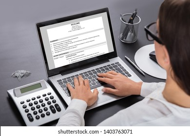 Close-up Of A Businesswoman Looking At Resume On Laptop At Workplace