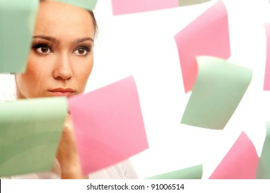 Closeup of a businesswoman looking at stickers, isolated on white background