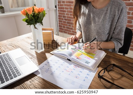 Close-up Of A Businesswoman Making Agenda On Personal Organizer At Workplace