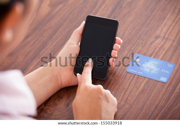 Close-up Of Businesswoman Paying With Credit Card On Mobile Phone