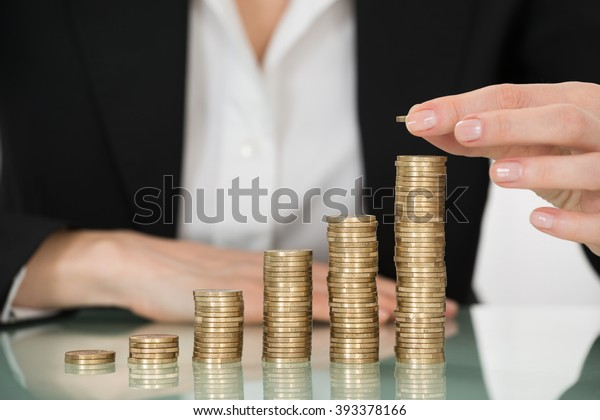 Close-up Of Businesswoman Placing Coin Over Stack Of Coins