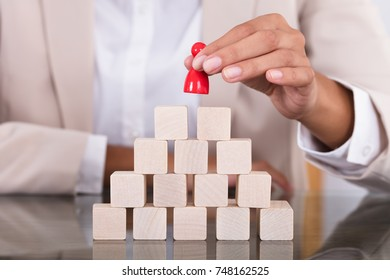 Close-up Of A Businesswoman Placing Red Figure On Arranged Blocks Over Desk