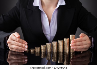 Close-up Of Businesswoman Protecting Golden Coins With Hand