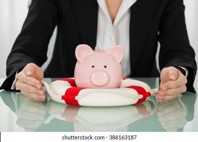 Close-up Of Businesswoman Protecting Piggybank With Lifebelt