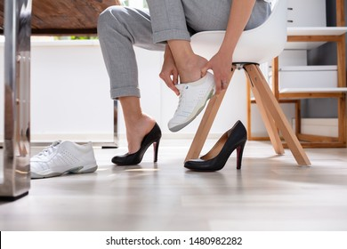 Close-up Of Businesswoman Removes Black Shoes And Wears Comfortable White Sneakers In Office