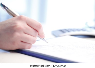 Close-up of a businesswoman sign the contract while sitting at desk in office.