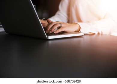 Closeup of businesswoman typing on laptop computer.