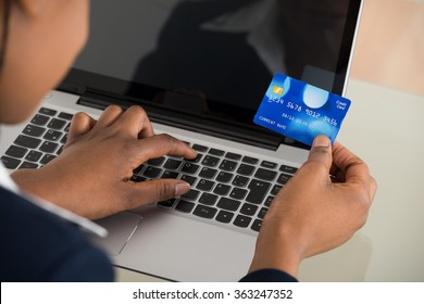 Close-up Of A Businesswoman Using Debit Card While Shopping Online