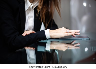 Closeup of a businesswoman using a tablet refelcted in a glass table