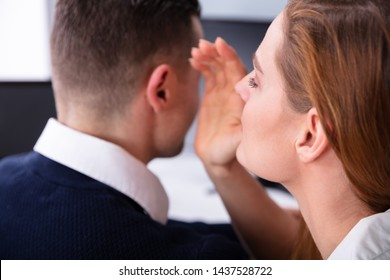Close-up Of Businesswoman Whispering Into Male Partner's Ear