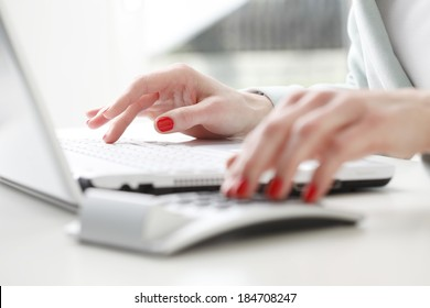 Close-up of businesswoman working on accountancy  with laptop. Small business.