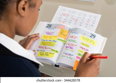 Close-up Of Businesswoman Writing Schedule In Calendar Diary