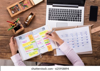 Close-up Of Businesswoman Writing Schedule In Calendar Diary On Desk