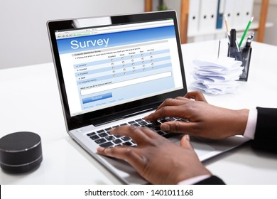 Close-up Of A Businesswoman's Hand Filling Online Survey Form On Laptop In Office