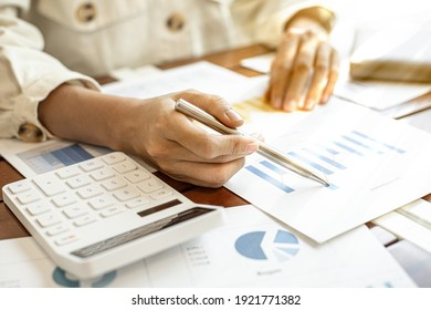 Close-up businesswoman's hand holding a pen pointing at a bar chart on a corporate financial information sheet, the businesswoman examines the financial information provided by the finance department.