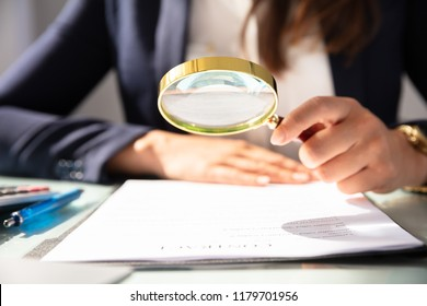Close-up Of A Businesswoman's Hand Looking At Contract Form Through Magnifying Glass