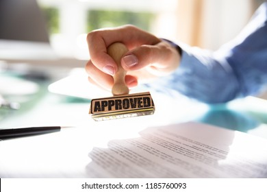 Close-up Of A Businesswoman's Hand Stamping On Approved Contract Form