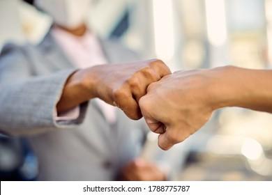 Close-up of businesswomen fist bumping while greeting during coronavirus pandemic.