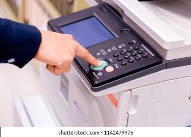 Close-up bussiness man Hand press button on panel of printer, printer scanner laser office copy machine supplies start concept.
