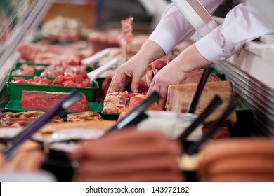 Closeup of butcher's hands arranging meat in display cabinet at shop