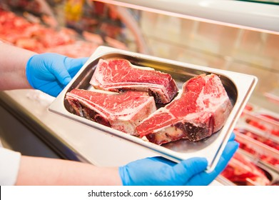 Close-up of butcher's hands holding meat piece in shop