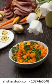 Closeup of butternut squash with green peas sidedish for delicious spicey roasted Easter ham dish, deviled eggs, asparagus, baby carrots, strawberries, and Easter decoration.