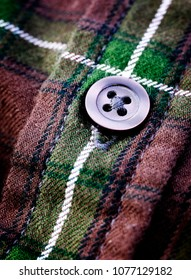 Closeup of button on plaid flannel shirt