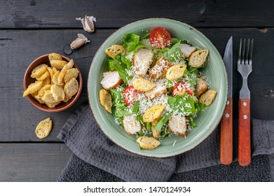 Close-up Caesar salad with fried chicken, parmesan and croutons on a dark rustic background. Top view