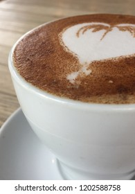 Close-up of Cafe Latte in a white cup on a wooden table