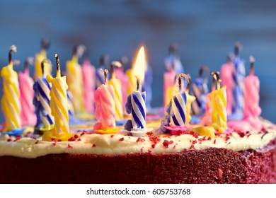 closeup of a cake with some unlit candles and just one lit candle after blowing out the cake