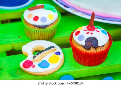 closeup cakes and cookies in a palette on a green background - Shutterstock ID 496098154