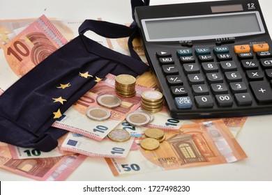 Die als Flagge der Europäischen Union konzipierte Nahaufnahme eines Taschenrechners, von Euro-Rechnungen und Tagesmasken, die das Konzept der Wirtschaft symbolisieren, wird durch die Epidemie mit dem Coronavirus verursacht.