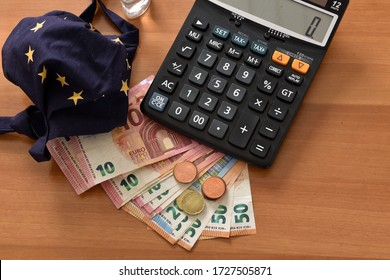 Close-up of a calculator, euro bills and diy facemask, designed as an European Union flag, symbolising the concept of economy fall due to the coronavirus epidemic crisis.