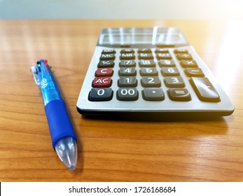 Closeup of a calculator and a pencil arranged on a table to convey the concepts of tax season and monthly expenses