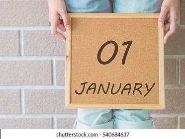 Closeup calendar at the cork board in hand of asian woman in front of her legs with 1 january word on brick wall textured background