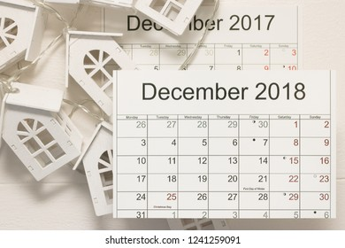 Close-up: calendar December 2018 is on background of old calendar of last year and a festive garland of wooden houses. Concept: summarizing the past year. Life and business.